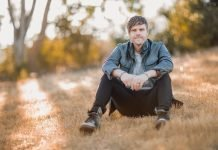 Jason David Slitter sits on the grass