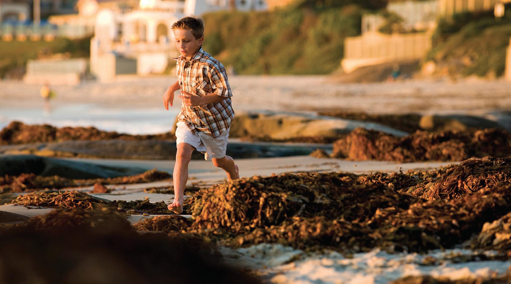 a boy runs on the beach