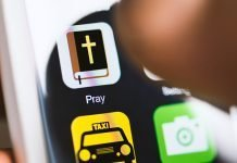 Hand holding phone, touching pray app on screen