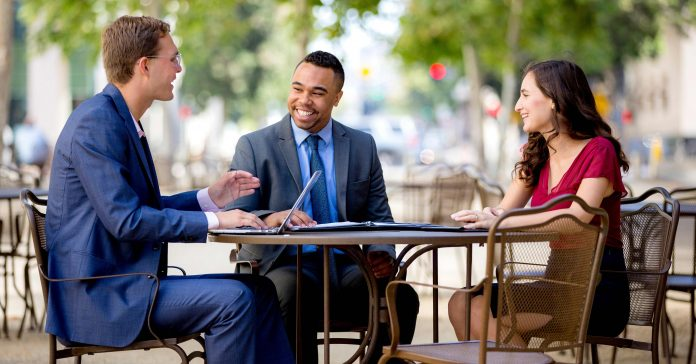 A group of businesspeople have an outside conversation.
