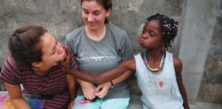 Two PLNU students laugh with a young girl on a Loveworks Trip