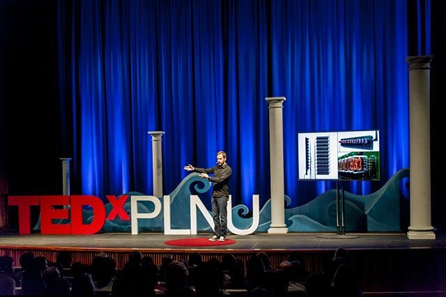 A PLNU professors presents on stage at TEDxPLNU