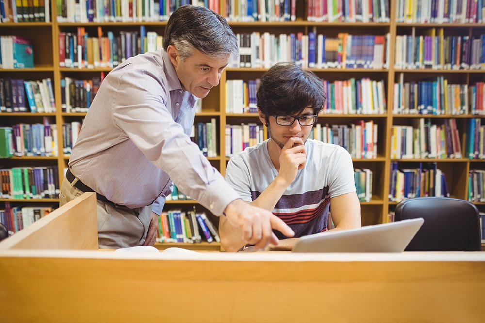 Professor assisting a student with studies in college library