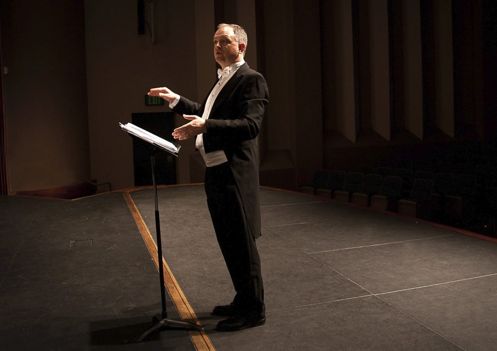 A music conductor gives instructions at the front of the stage.