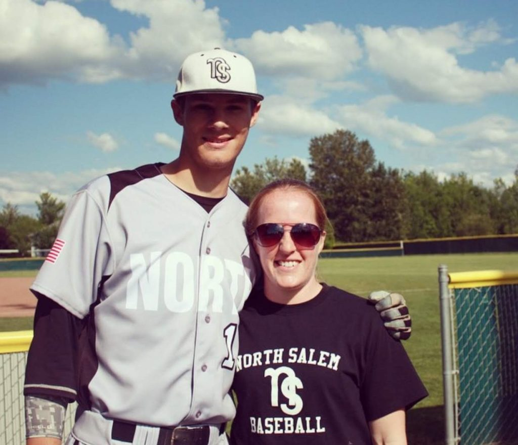 Isaiah Yoder in a baseball uniform stands next to his athletic trainer from high school.