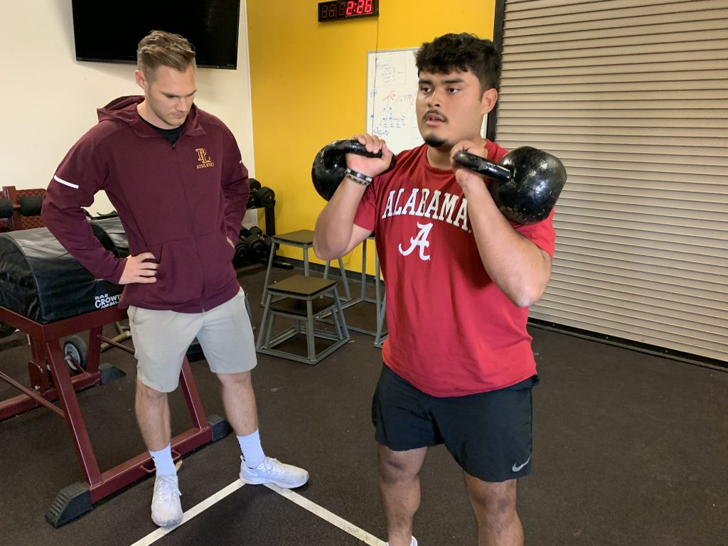 Isaiah Yoder looks on as a student performs a weight lifting move.