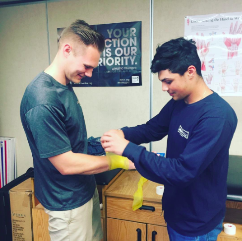 A student learns how to wrap tape around an athlete