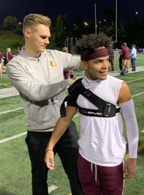 Yoder applies a brace to a football player.