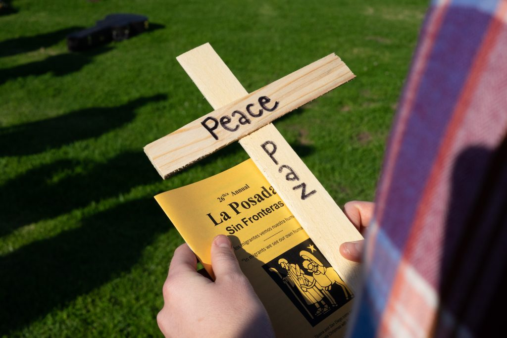 "Someone holding a cross with ""peace"" written on it."