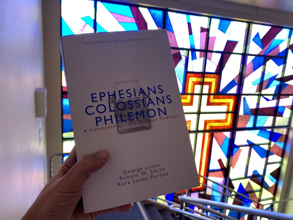 Hand holds up a copy of Ephesians, Colossians, Philemon commentary book.