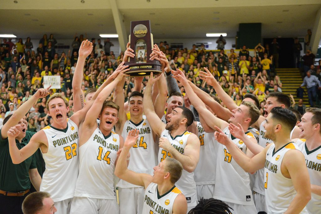 Daulton Hommes (center) pictured holding up the NCAA Division II Regional Champion trophy with the 2018-2019 PLNU Men's Basketball team.