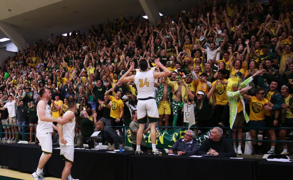 Daulton Hommes jumps onto the scorers table after PLNU's Men's Basketball team after winning the regional final.