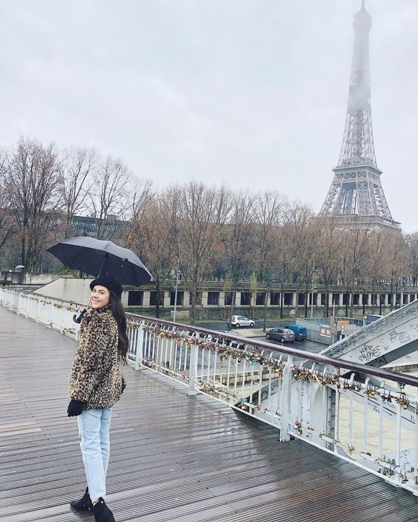 Emma Mitchell walks with an umbrella near the Eiffel Tower in Paris.