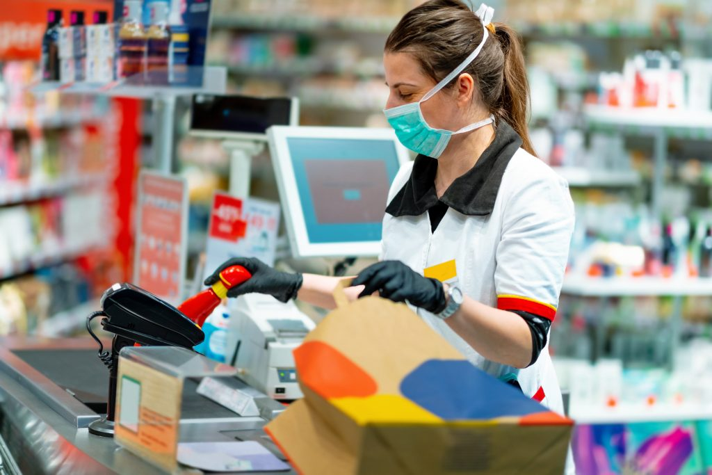 Grocery store cashier wears a mask and gloves while working.