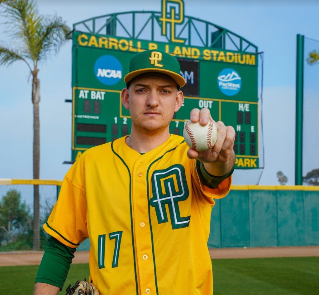 Zack Noll posing for a photo in his PLNU uniform with a baseball.