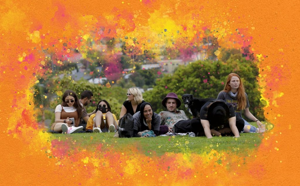 Young people sitting on the grass with a colorful border around the photo
