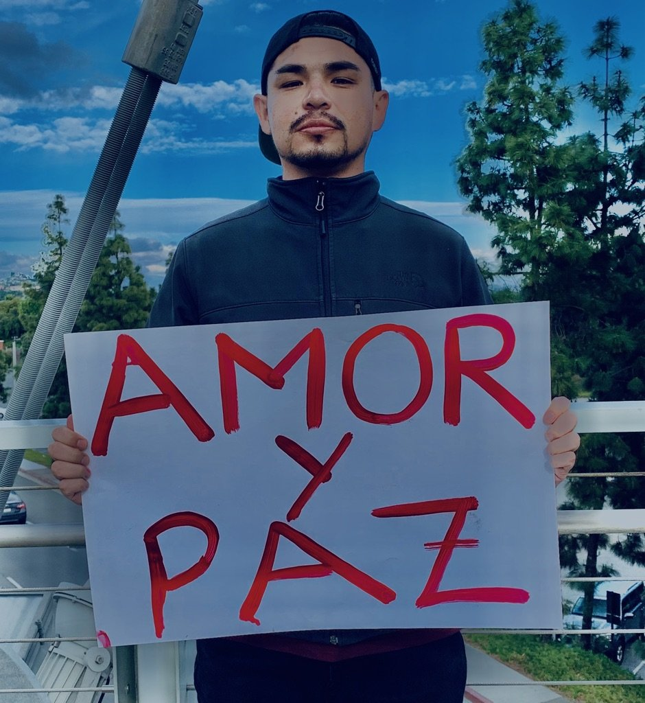 "Jonathan holding a sign that says ""Amor y Paz"""