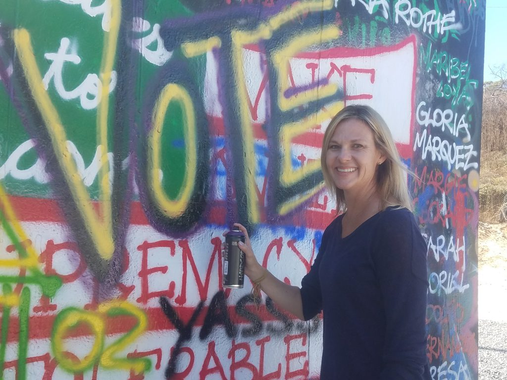 Lindsey Lupo next to graffiti that says vote