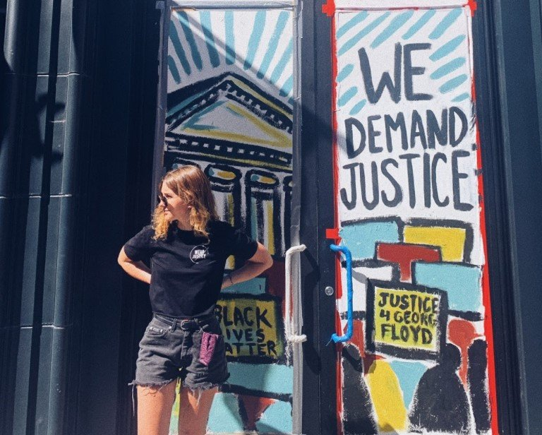 "Elaine Giles next to art that says ""We Demand Justice"""
