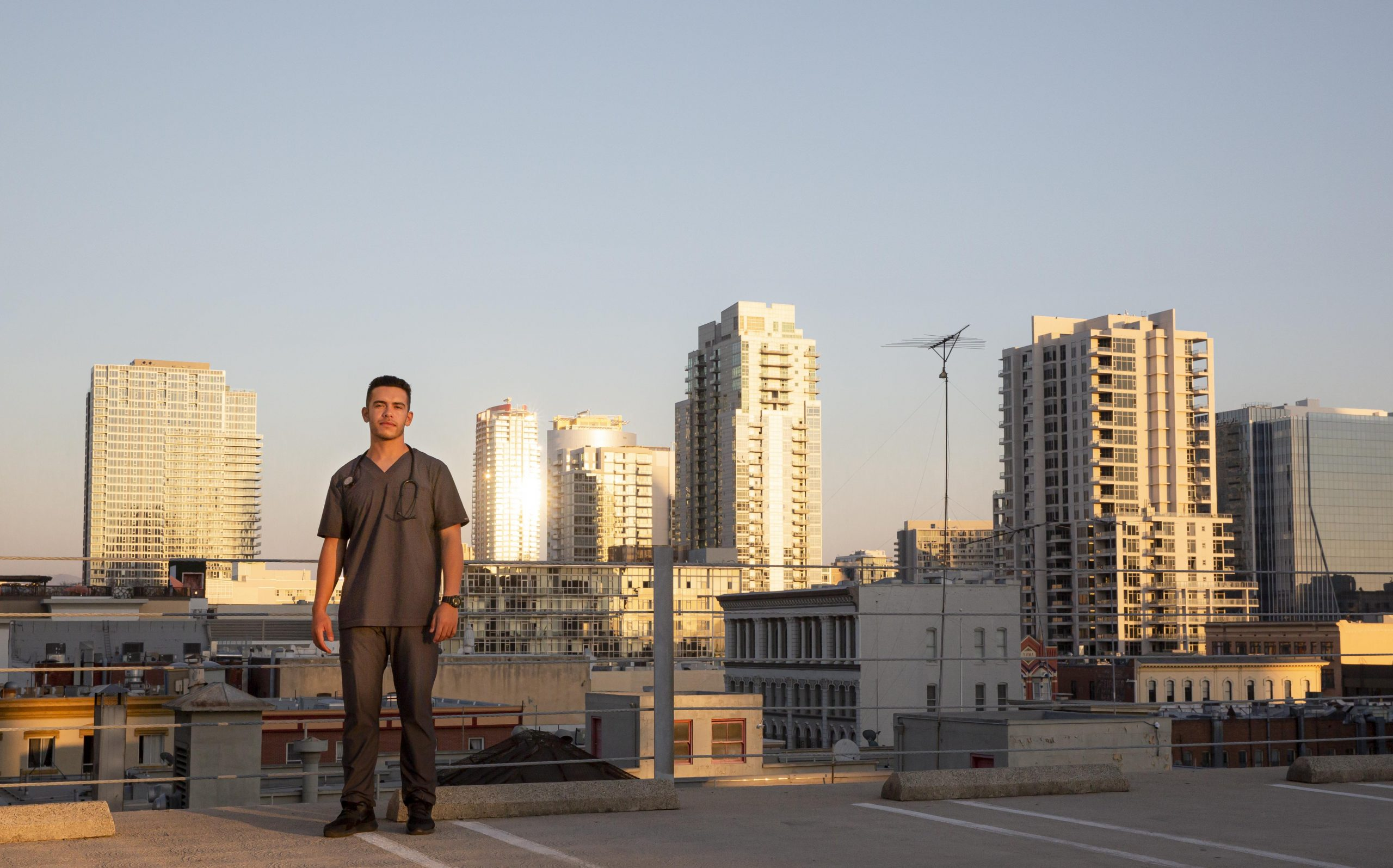 Elias in scrubs with the city in the background