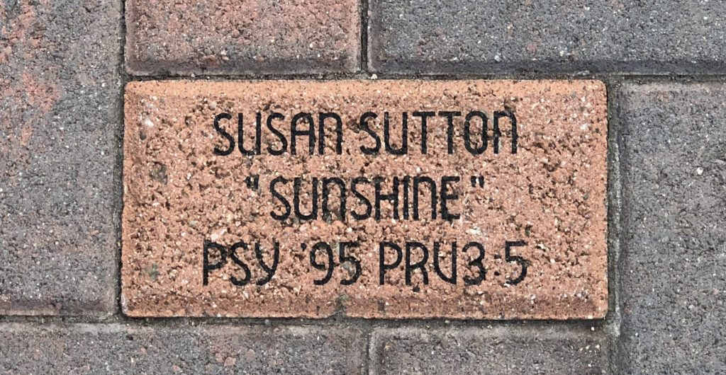 A brick with words and a Bible verse on it