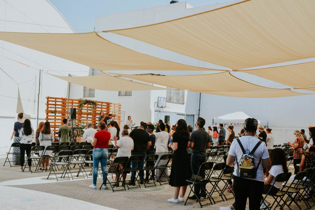 A church gathers outside to worship.