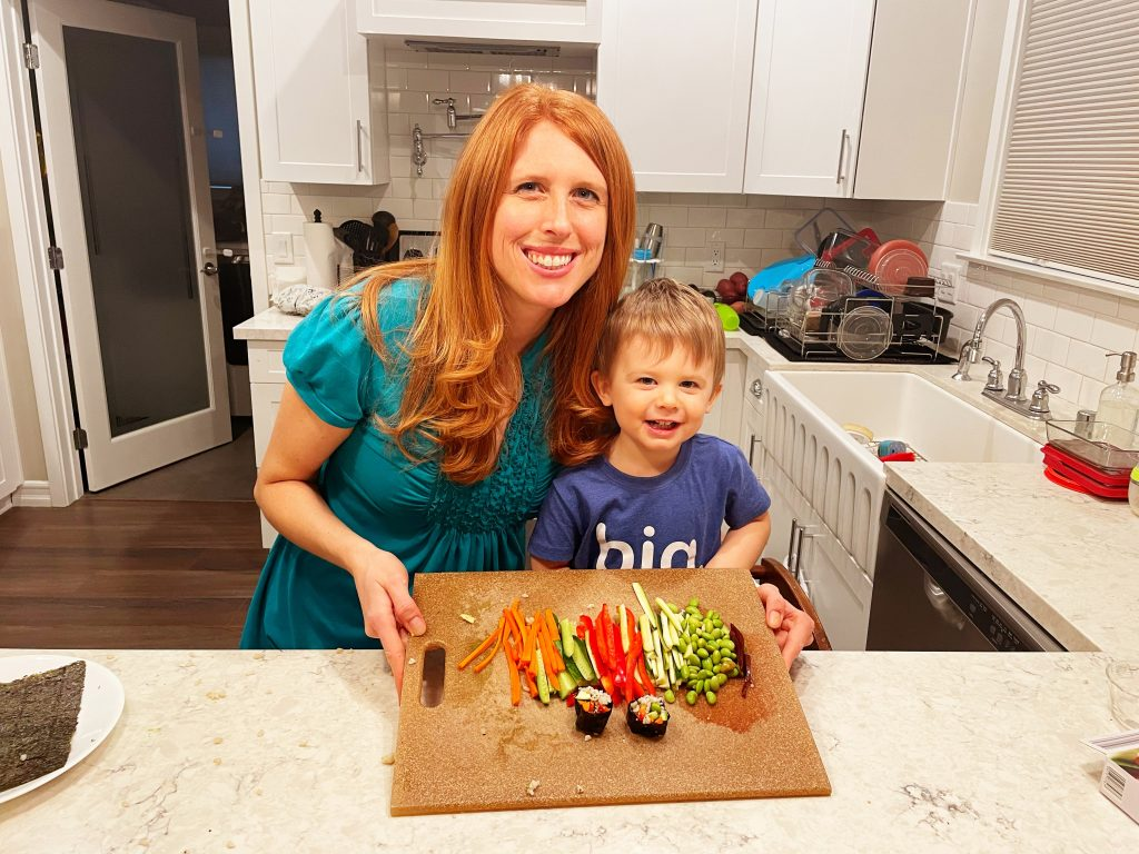 Nemeth at a chopping board smiling with her son